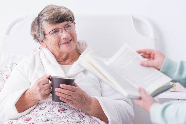 Elderly woman being read to in hospital