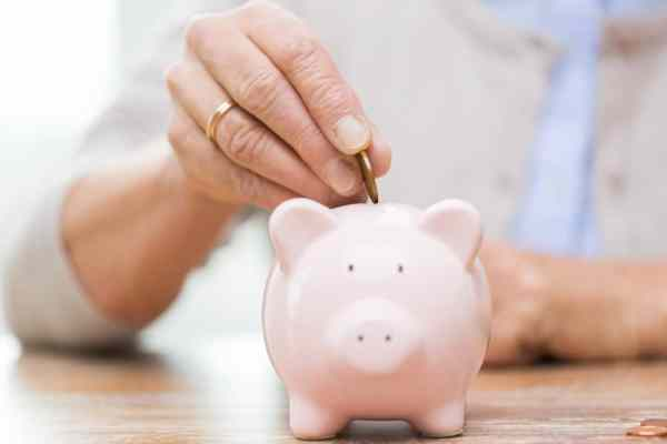 elderly woman putting coin in pension piggy bank