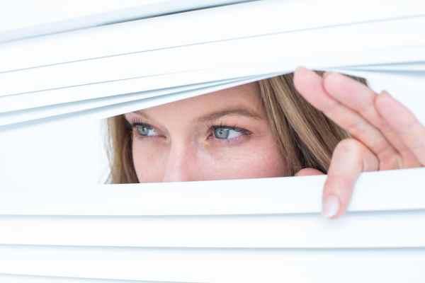 Woman spying through a window blind
