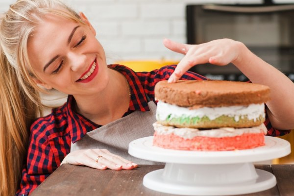Young woman making a tired cake