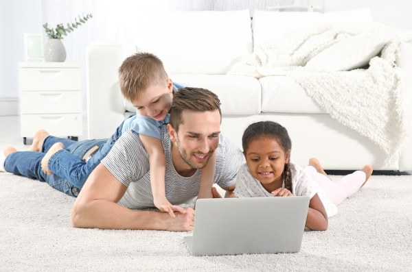Foster father with children using laptop