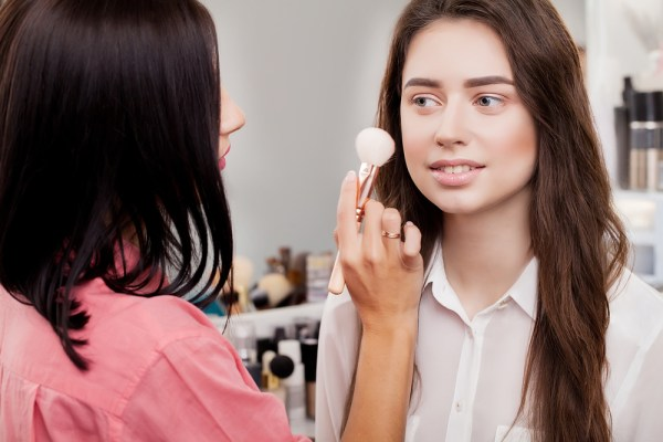 Woman applying makeup to potential buyer