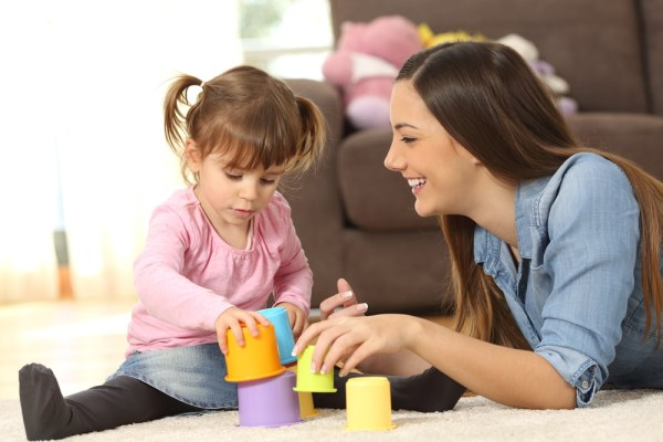 Young woman playing with toys with young girl