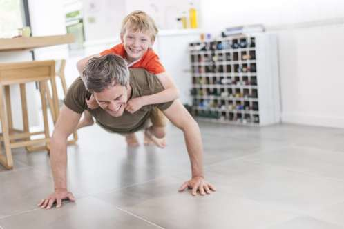 Father doing push up with young son on his back