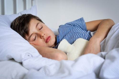 Young boy in bed asleep with hot water bottle