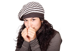 Young woman wearing woolly hat breathing on her hands to keep warm