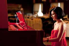 Young woman in red dress playing piano in restaurant