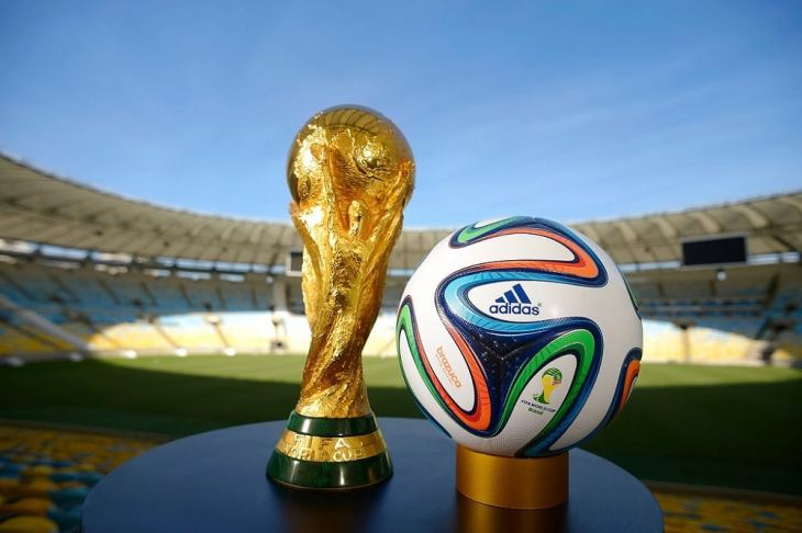 world cup football and trophy with stadium in the background