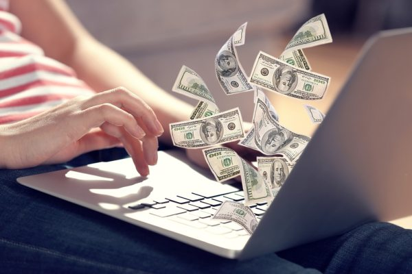 Laptop with cash floating out of it