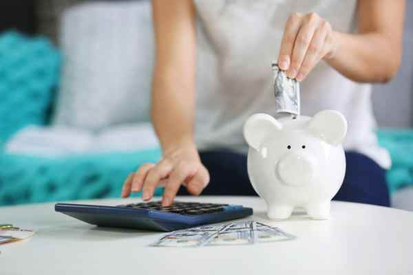 Woman saving money in piggy bank and using a calculator