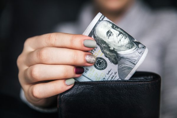 Woman with manicured nails holding cash