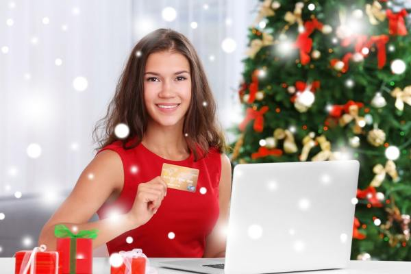Festive woman shopping online with credit card