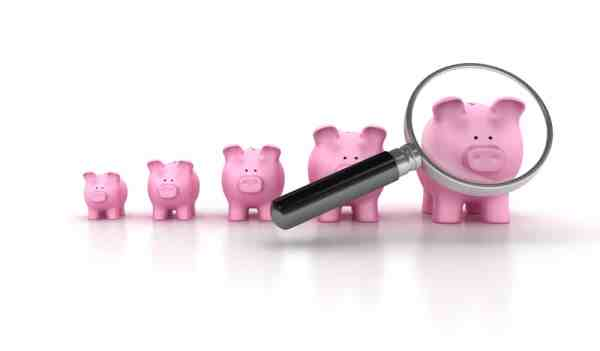 Magnifying glass and different size piggy banks