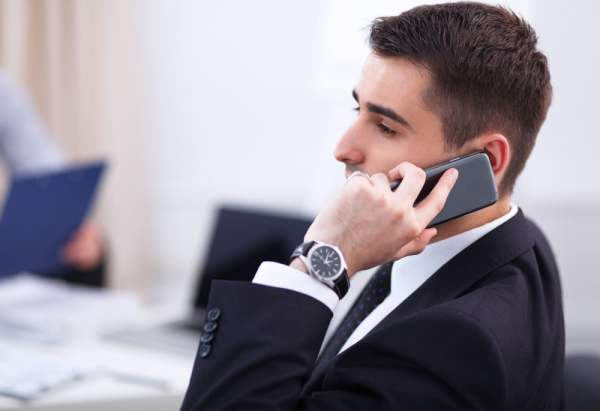 Man answering his phone in a meeting