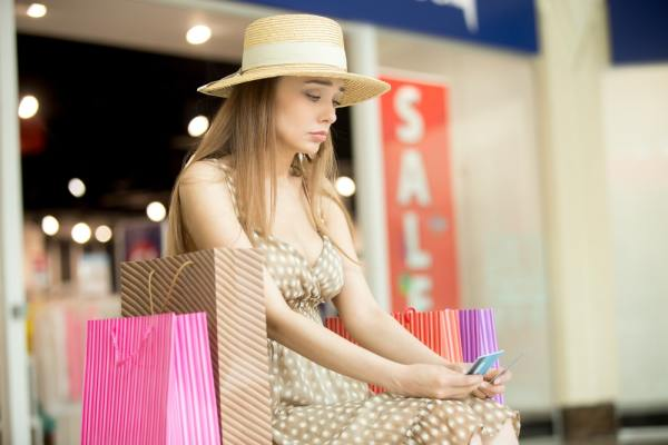 Unhappy woman after spending too much on shopping