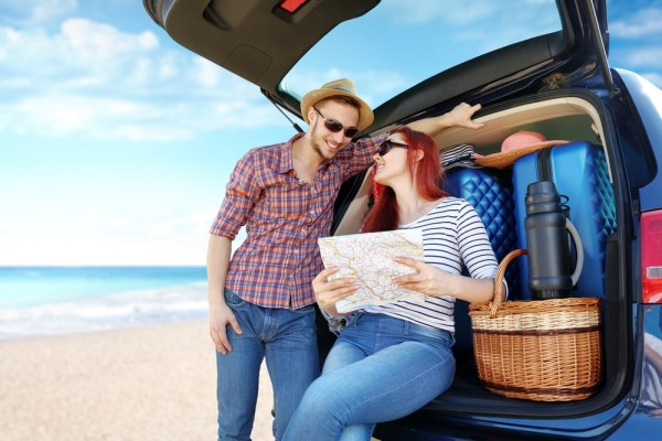 Couple at the beach with their car full of suitcases