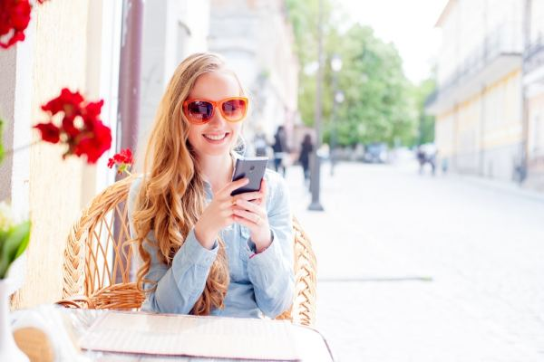 Young Woman using smartphone outside a cafe in the sunshine