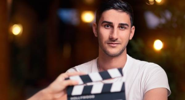 Male actor behind clapper board