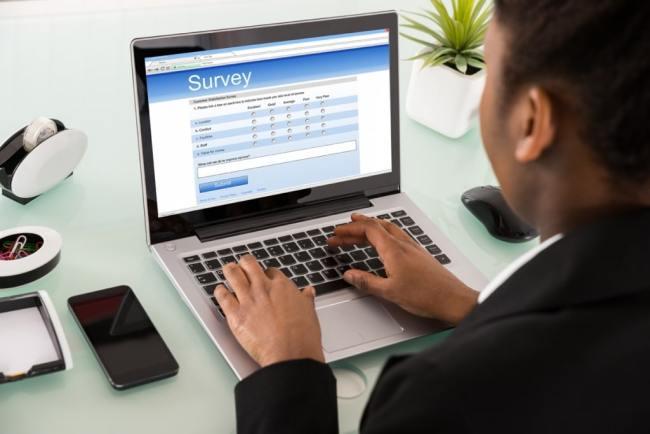 Asian business man completing online surveys on a laptop