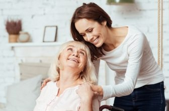 Woman carer smiling at elderly patient