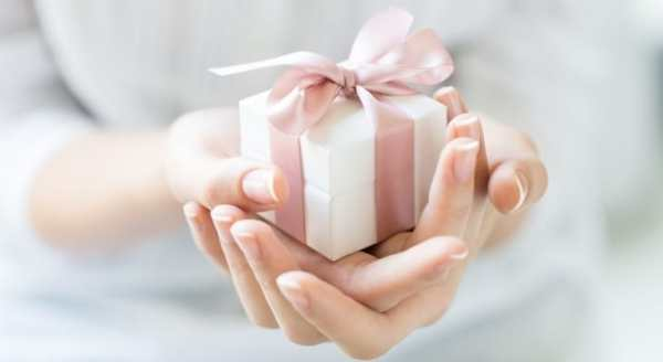 Womans hands holding small gift with pink ribbon