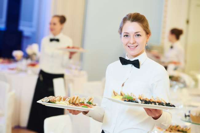 Young woman wearing catering uniform and holding plates of food