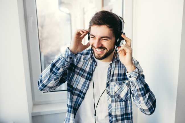 Happy man listening to music on headphones