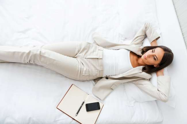 Woman relaxing on hotel bed