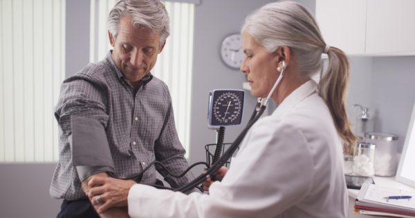Middle aged man getting a blood pressure check at the doctors