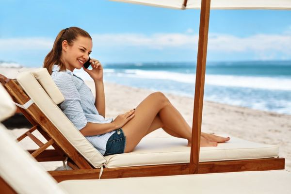 Woman using mobile phone while sitting on a lounger on the beach