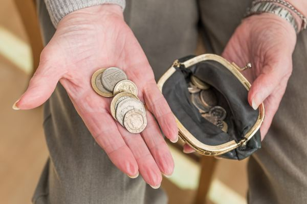 Elderly woman holding pound coins
