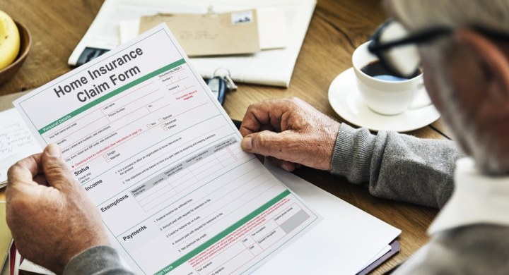 Senior looking at a home insurance claim form
