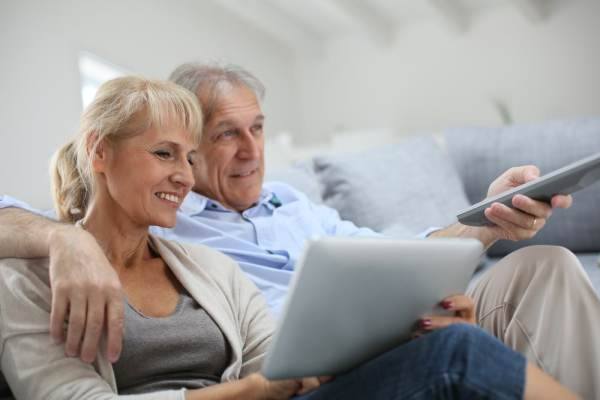 Elderly couple at home watching TV and using a tablet