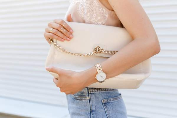Woman holding designer handbag and wearing designer watch