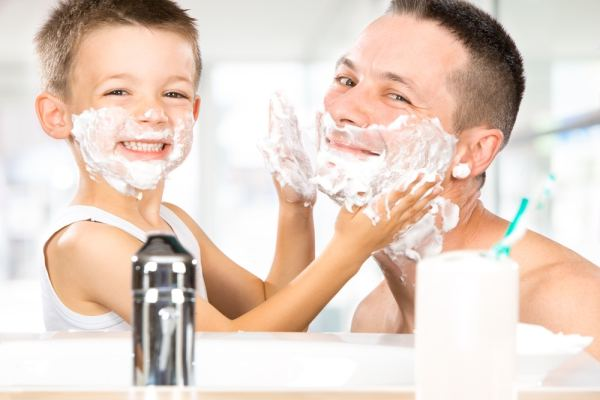 Father and son with shaving foam on their faces