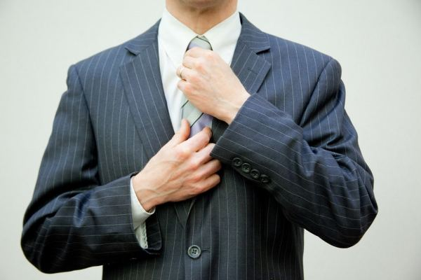 Professional man in a suit adjusting his tie