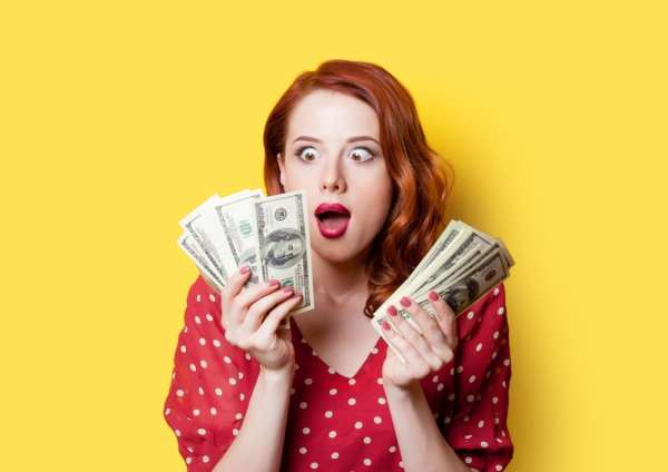 Woman looking at money in surprise