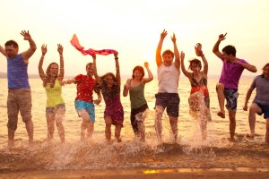 Group of young adults jumping happily in the sea
