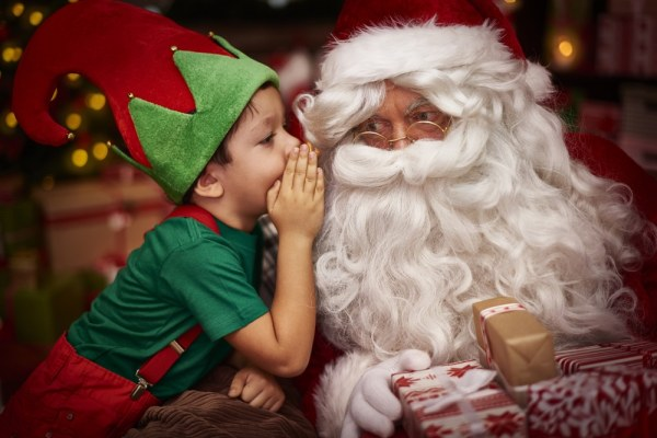 Little boy in elf costume whispering to santa