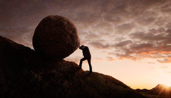 Effort concept - man pushing large boulder up a hill