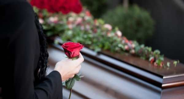 Someone standing by a coffin holding a rose