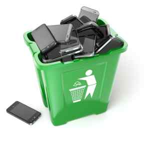 Green recycle bin with old mobile phones in