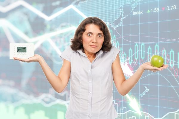 Worried woman holding apple and thrmostat