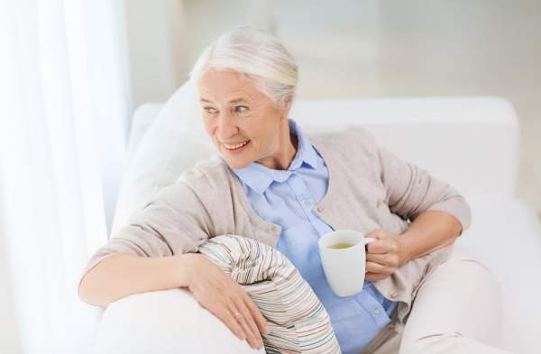 Elderly woman relaxes on the sofa with a cup of tea