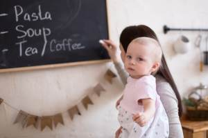 Mother writing foods on a blackboard with a toddler standing by