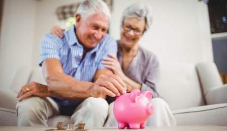 Over 60s make money - Elderly couple putting money in a piggy bank