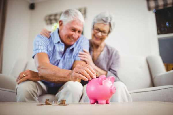 Over 60s couple putting money in a piggy bank