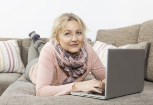 Older woman lying on her stomach on the sofa smiling and using a laptop computer