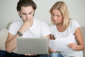Man and woman working through their finances on a laptop
