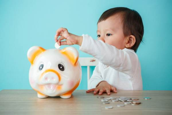 Baby putting money in piggybank